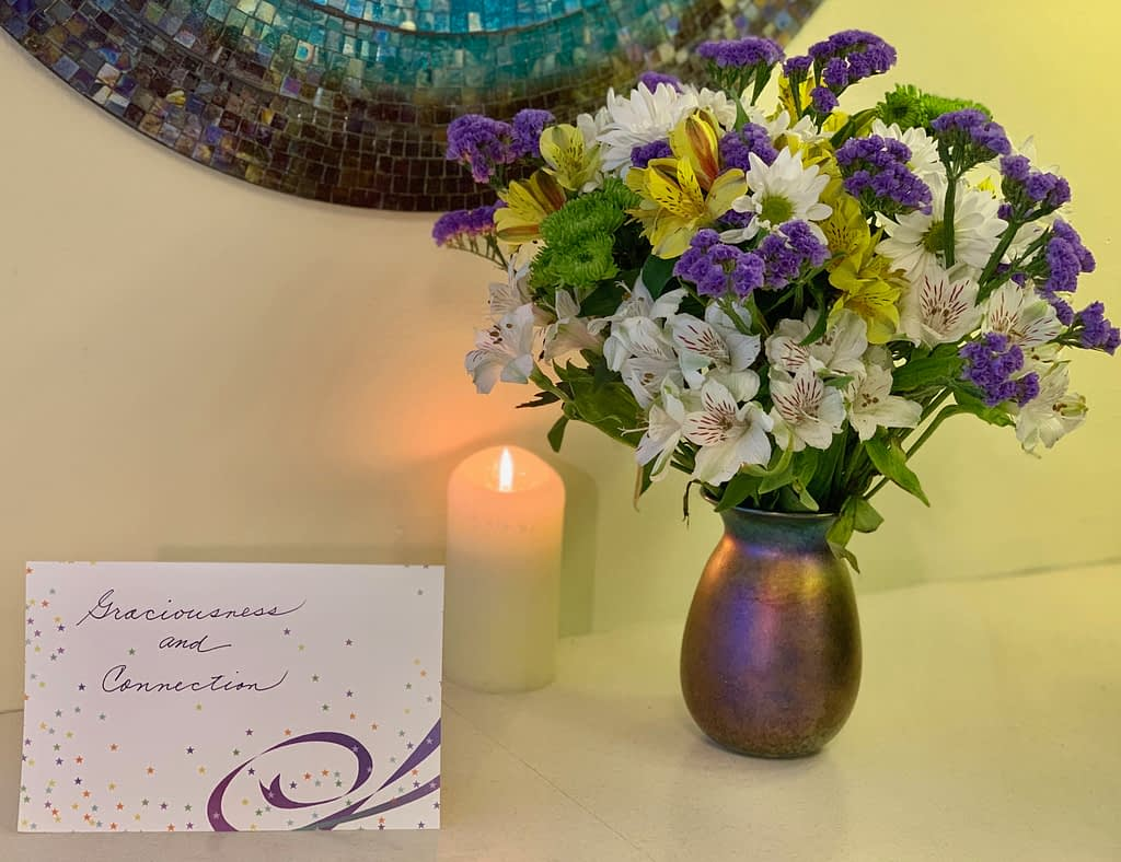 Celebrating with a beautiful bouquet of flowers, a candle and a card, Toni Gattone Resilient Gardener speaker and author blogs about her Intentions for 2020: Graciousness and Connection.